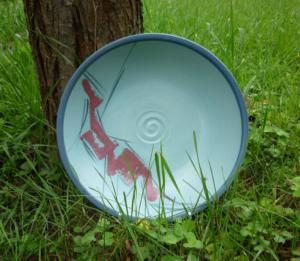 Schale mit rotem Pinseldekor an einen Baumstamm gelehnt