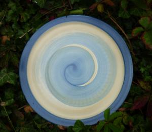 Großer Teller in Gelb-Blau liegt im Efeu