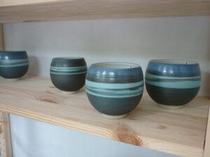Vier Teeschalen in Türkis-Blau auf einem Regal