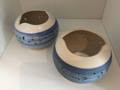 Zwei Windlichter in Blau auf Creme mit ausgeschnittenen Elementen